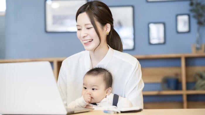 赤ちゃんを抱えてパソコンをするママ