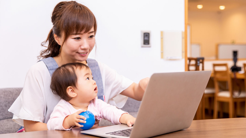 赤ちゃんを抱えてパソコンをするお母さん